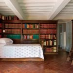 duvarlari komple kaplayan kitaplik ve ortasinda yatak